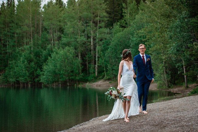 Bride and groom posing in front of the water in Kananaskis. Bride is looking back at the groom as they walk away.