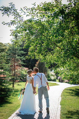 bride and groom on a path surrounded by trees sharing a kiss.