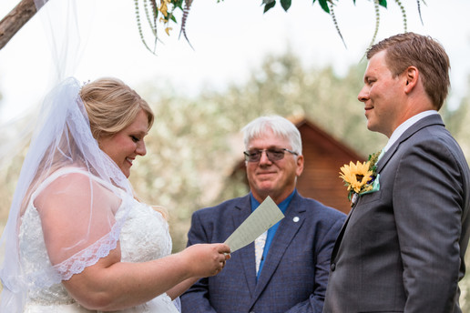 Bride and groom exchanging vows under an archway. One of the dads is officiating.