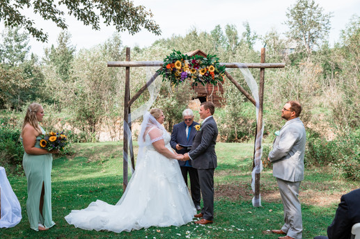e Bride and groom standing under an archway adorned with flowers, tule and greenery. One of the dads is officiating.