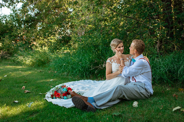 bride and groom sitting on the grass and the groom is holding the brides face with one hand.