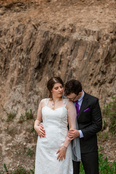 Groom kissing his brides shoulder standing in front of a mountain in Banff National Park