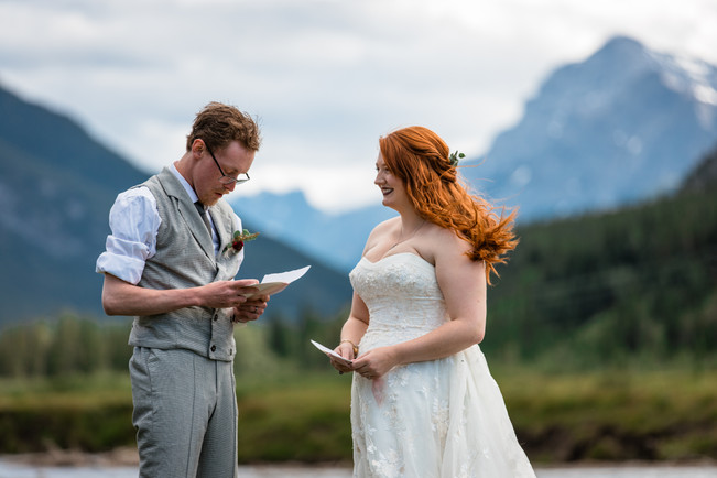 Bride and groom reading from their vow booklet in front of the water with the mountains in the background.