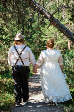 Bride and groom walking away holding hands on a path surrounded by trees.