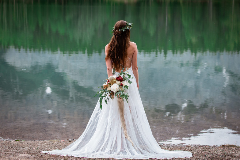 Bride facing the water showing the back of her dress and bouquet.
