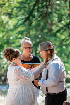 Bride putting a necklace on the groom that holds his wedding rings.