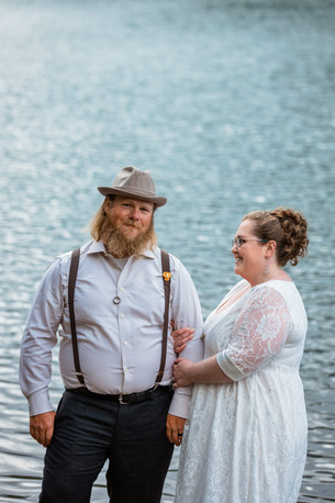 Bride and groom standing in front of the water. Bride is looking at the groom smiling.