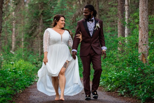 Bride and groom walking on a pathway through trees looking at one another smiling.