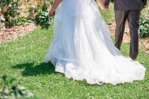 The bride and groom standing in a beautiful garden, shot from behind, showing the couple holding hands.