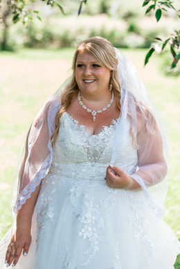 Photo of the bride showing the detail of the top of her dress and her jewelry.