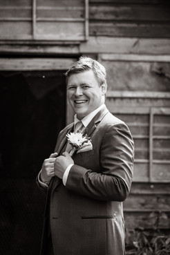 Black and white photo of the groom smiling holding his suit jacket together.