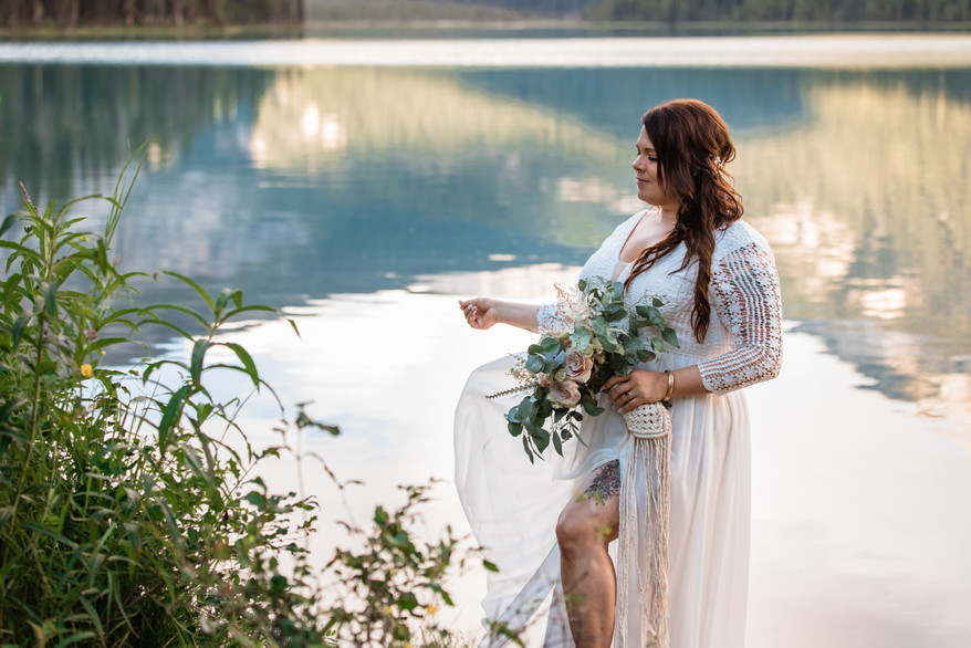 Bride standing at the water looking down. Reflection in the water behind her.