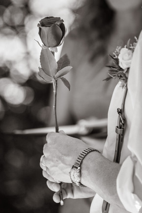 black and white photo of the groom holding a flower.