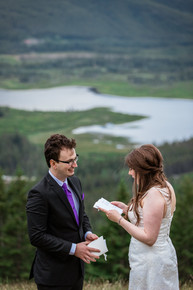 Bride and groom reading personalized vows hand written in a booklet. At a lookout at Banff National Park.