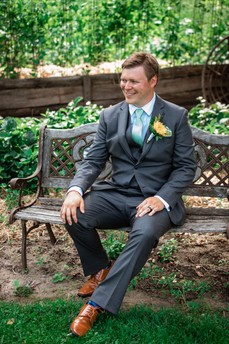 Groom sitting on a old metal and wooden bench. You can see the grooms wedding ring and boutonniere.