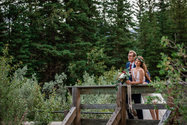 Bride and groom standing on a wooden bridge looking out over the water.