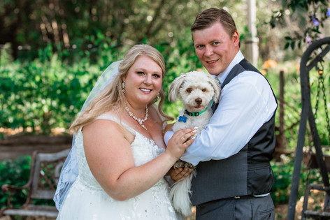 Bride and groom posing with their dog on a bridge.