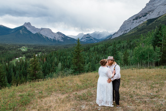 Bride and groom kissing in the middle of a clearing surrounded by trees and mountains.