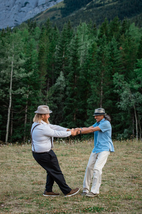 Groom and his best man holding hands and spinning around in a clearing in front of the tall trees.