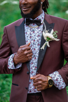 Groom's suit and boutonniere up close. Burgundy and black and suit jacket with a white shirt that has flowers on it matching the suit.