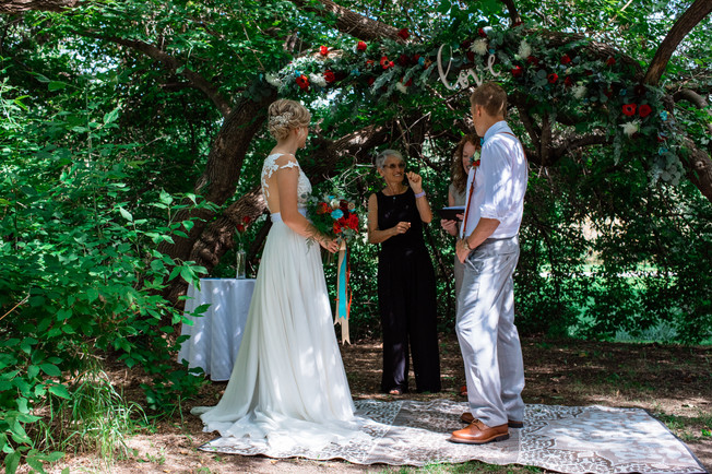 bride and groom under a big tree exchanging vows.