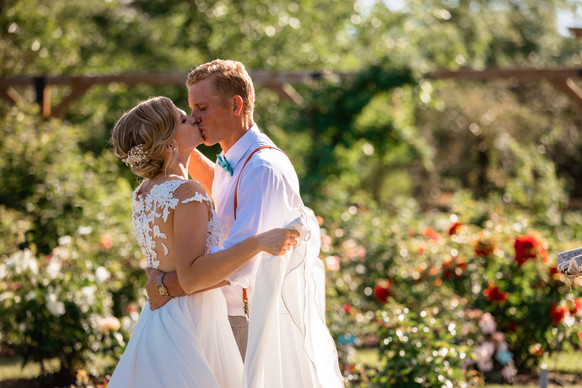 bride and groom kissing in a pretty garden.
