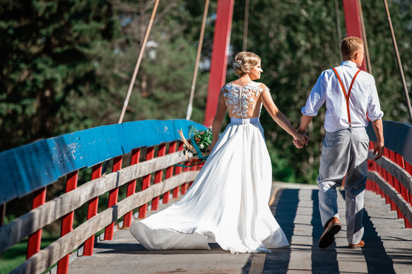 bride and groom walking across a suspension bridge hand in hand looking out on the water.
