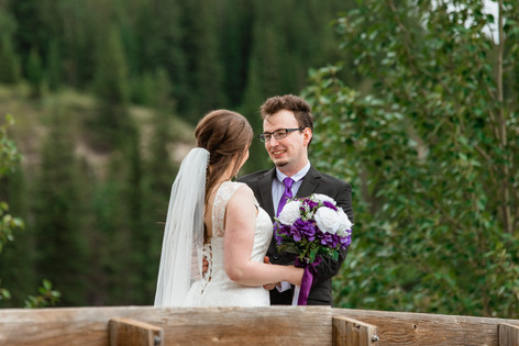 Bride and groom standing on a wood bridge over the water at Cascade ponds. Bride is holding her bouquet.