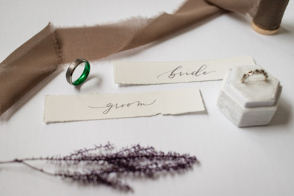 Bride and groom flat lay showing rings and details.