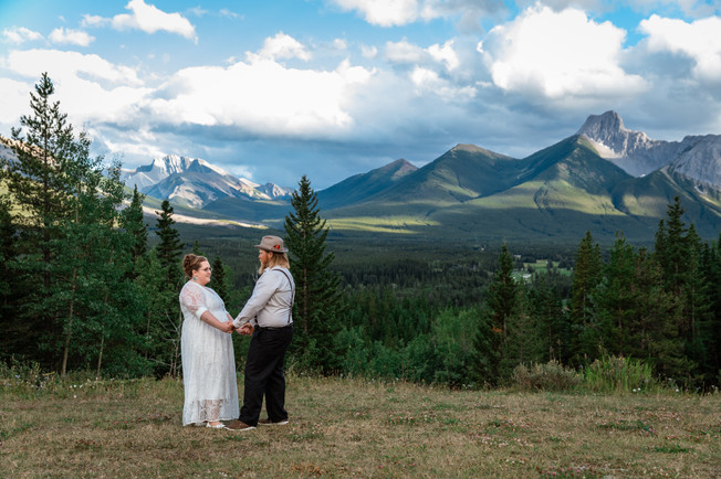 Couple standing in front of one another and holding hands. Trees and mountains behind them.