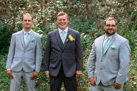 Groom standing with his groomsmen in front of the trees.