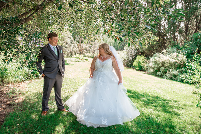 Bride showing her dress to the groom standing in a beautiful garden.