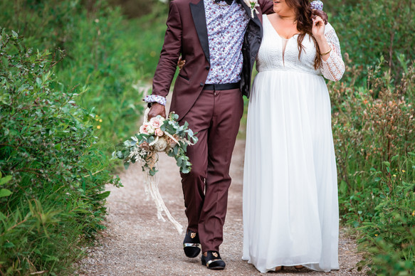 Bride and groom walking on a path. Groom has his arm around her shoulders and is carrying her bouquet.