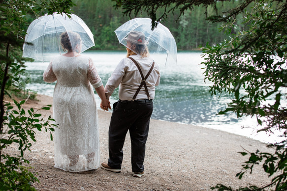Bride and groom walking along the water holding clear umbrellas.