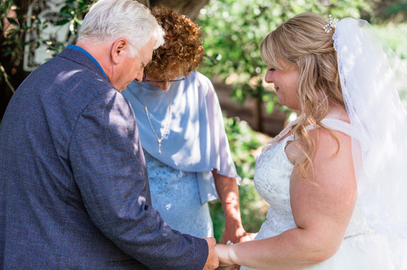 The bride holding hands with her mother and father saying a prayer.