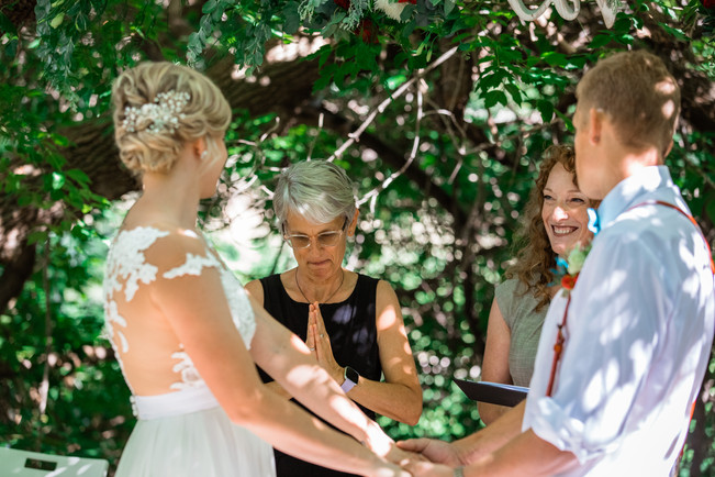 bride and groom holding hands in front of their officiant and deaf interpreter.