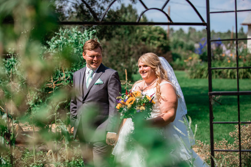 Bride and groom walking holding hands. Groom is looking at his bride smiling. Bride is holding her bouquet.