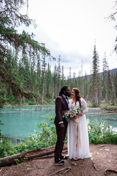 Bride and groom standing together in front of Emerald Lake, Groom is kissing his bride on the cheek.