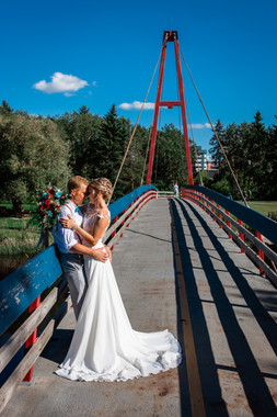 the bride and groom leaning against the suspension bridge holding one another closely.