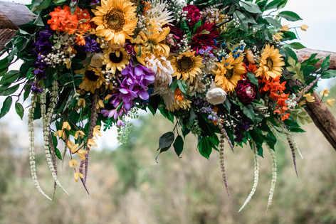 Wooden archway adorned with flowers, greenery and tule.