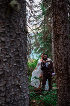 Bride and groom standing between big trees. Bride is standing behind the groom with her arm around his shoulder.