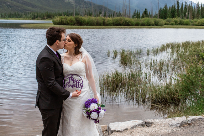 Bride and groom holding a wooden sign of their new chosen last name in front of the water