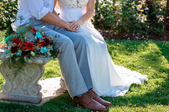 bride and groom sitting on a pretty concrete bench touching hands. Bridal bouquet is showcased.