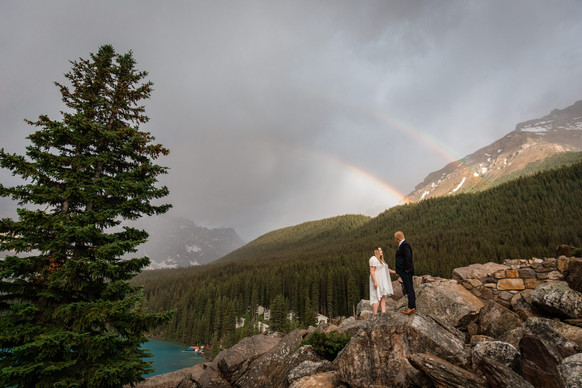Couple standing on the rocks with a double rainbow behind them, mountains and trees.
