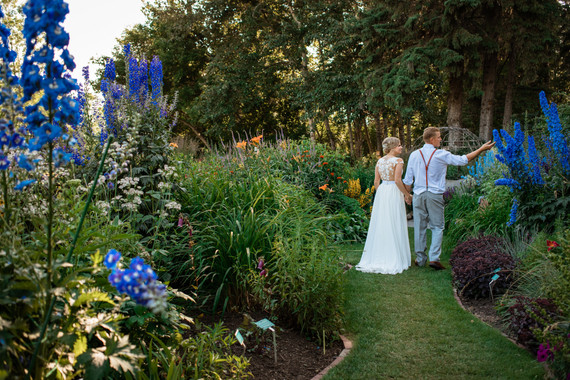 bride and groom walking down a path with tall flowers on either side of them.