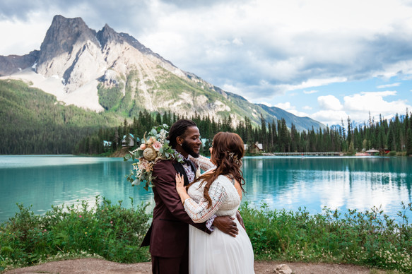 Bride and groom holding one another in front of gorgeous Emerald Lake and a mountain.