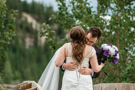 Bride and groom hugging on a wood bridge over the water in Cascade ponds. Bride is holding her bouquet.