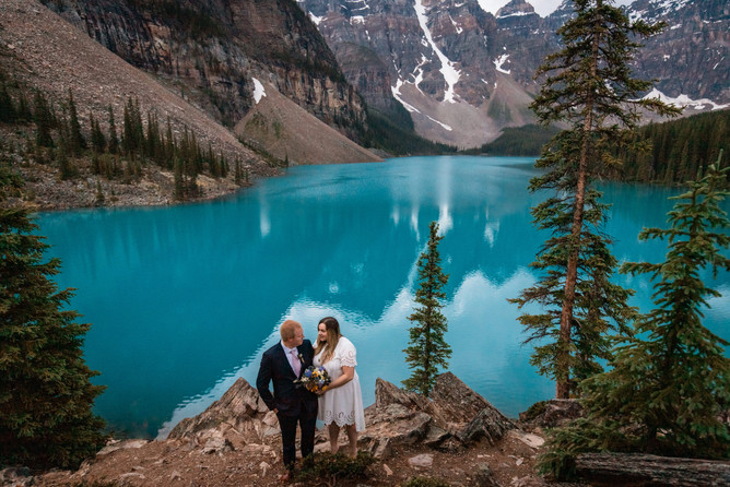 Bride and groom standing together looking at one another. Beautiful Moraine Lake in the background with mountains.
