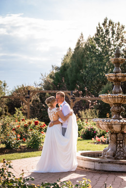 bride and groom embracing and kissing in a pretty garden.