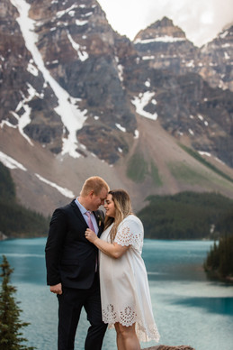 Couple embracing with the water and mountains behind them.
